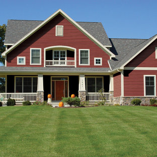 Example of a classic red two-story metal exterior home design in Grand Rapids with a shingle roof