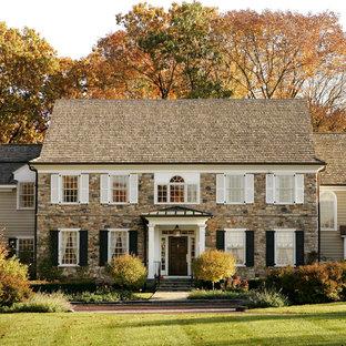 Aménagement d'une façade en pierre classique à deux étages et plus avec un toit à deux pans.