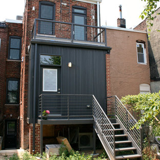 Example of a small trendy red three-story brick flat roof design in DC Metro