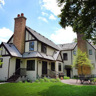 Example of a large classic beige two-story stucco gable roof design in Chicago