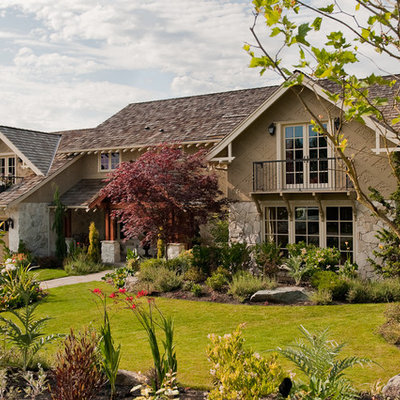 Large traditional beige two-story stone exterior home idea in Seattle