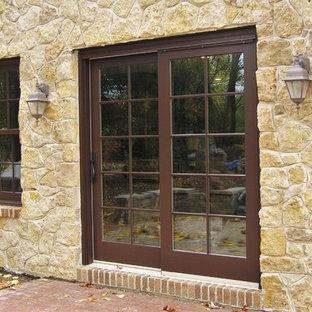 Foto de fachada marrón, ecléctica, de tamaño medio, de dos plantas, con revestimiento de piedra y tejado a dos aguas