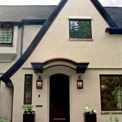 Large elegant beige three-story stucco exterior home photo in Portland with a shingle roof
