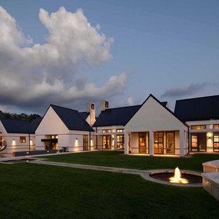 Foto de fachada de casa blanca, actual, extra grande, de una planta, con tejado a dos aguas, revestimiento de estuco y tejado de metal