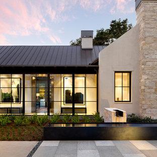 Пример оригинального дизайна: большой, одноэтажный фасад частного дома бежевого цвета в стиле модернизм с облицовкой из цементной штукатурки и металлической крышей