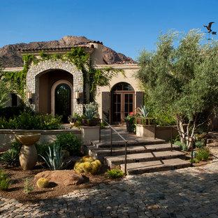 Diseño de fachada beige, mediterránea, de tamaño medio, de una planta, con revestimientos combinados y tejado plano