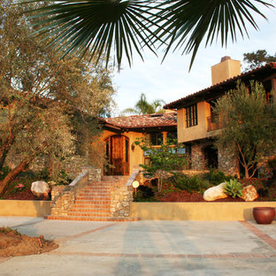 Large tuscan yellow two-story stucco exterior home photo in San Diego