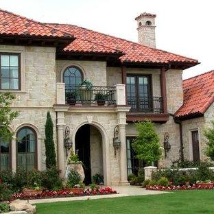 Ejemplo de fachada de casa gris, mediterránea, grande, de dos plantas, con revestimiento de piedra, tejado a cuatro aguas y tejado de teja de barro