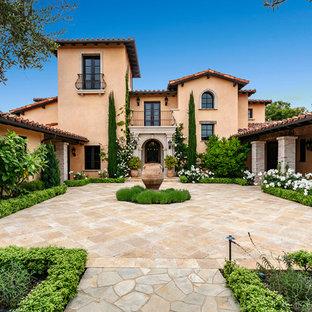 Стильный дизайн: трехэтажный, оранжевый частный загородный дом в средиземноморском стиле с двускатной крышей и черепичной крышей - последний тренд