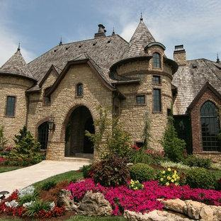 Foto della facciata di una casa unifamiliare grande marrone mediterranea a due piani con rivestimento in pietra e copertura a scandole