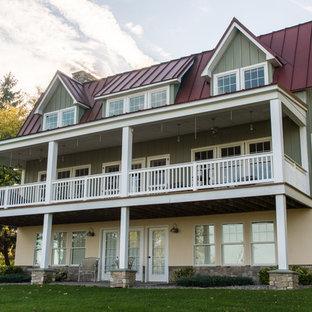 Foto de fachada verde, campestre, grande, de tres plantas, con revestimiento de madera y tejado a doble faldón