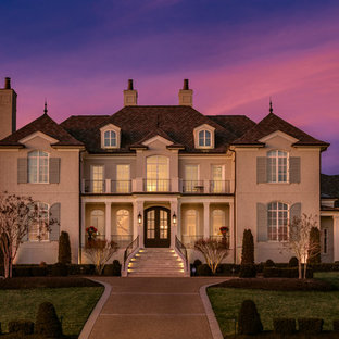 Inspiration for a timeless white two-story brick house exterior remodel in Nashville with a hip roof and a shingle roof