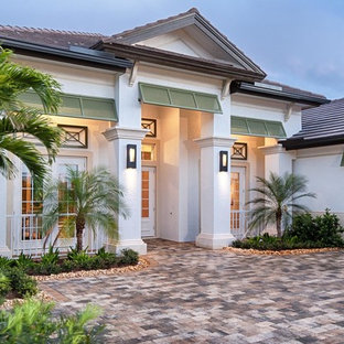 Transitional white one-story concrete exterior home idea in Miami with a hip roof