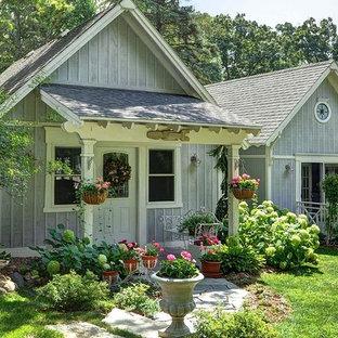Foto della facciata di una casa piccola grigia country a un piano con rivestimento in legno