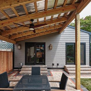 Imagen de fachada de casa gris, bohemia, extra grande, de dos plantas, con revestimiento de hormigón, tejado de un solo tendido y tejado de teja de madera