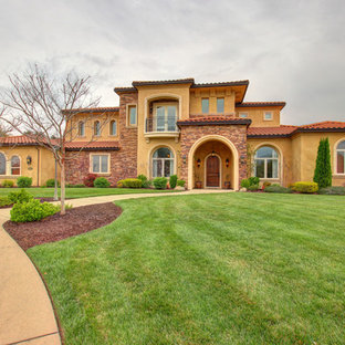 Example of a large tuscan orange two-story stucco house exterior design in Sacramento with a hip roof and a tile roof
