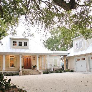 他の地域のおしゃれな家の外観 (木材サイディング、黄色い外壁) の写真