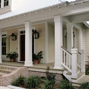 Diseño de fachada amarilla, grande, de dos plantas, con revestimiento de madera y tejado a cuatro aguas