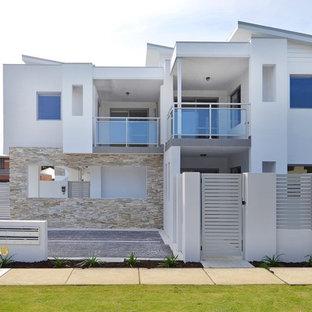 Modern inredning av ett mycket stort grått hus, med två våningar, pulpettak och tak i metall