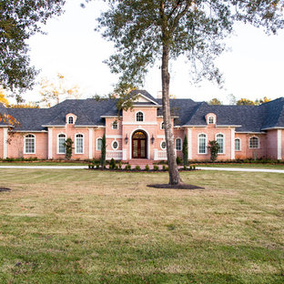 Photo of a large traditional one-storey brick red exterior in Houston with a clipped gable roof.