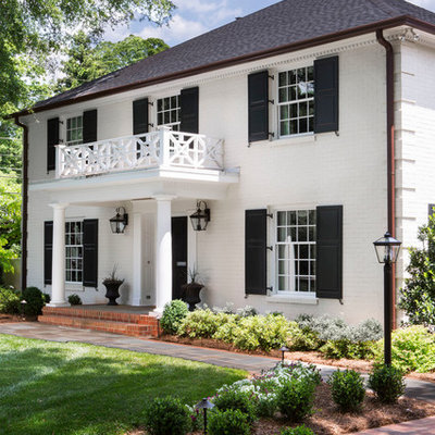 Example of a classic white two-story brick exterior home design in Charlotte with a hip roof