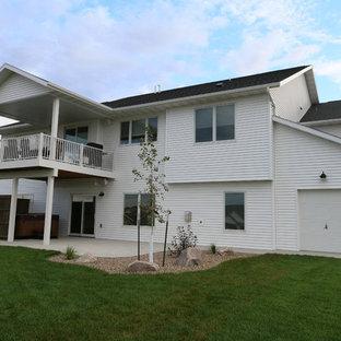 Diseño de fachada blanca, industrial, de tamaño medio, de una planta, con revestimiento de vinilo y tejado a dos aguas