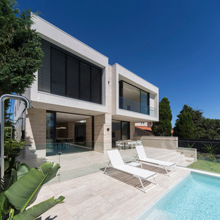 Large contemporary two-storey white exterior in Sydney with stone veneer and a flat roof.