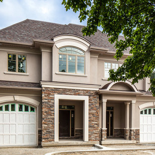 Large transitional beige two-story stucco exterior home idea in Toronto with a shingle roof
