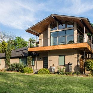 Immagine della facciata di una casa grande beige moderna a due piani con rivestimenti misti e tetto a padiglione