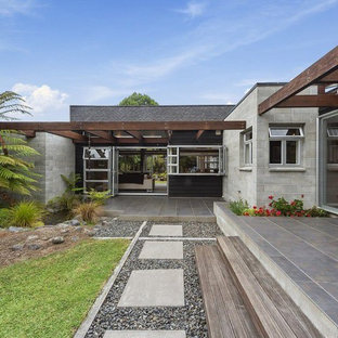 Mid-sized midcentury modern gray one-story concrete exterior home idea in Auckland with a shingle roof