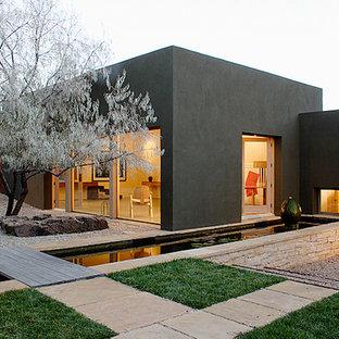 Exempel på ett stort modernt svart hus, med allt i ett plan och stuckatur