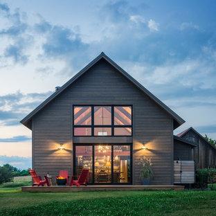 Foto de fachada de casa marrón, de estilo de casa de campo, de tamaño medio, de dos plantas, con revestimiento de madera, tejado a dos aguas y tejado de metal
