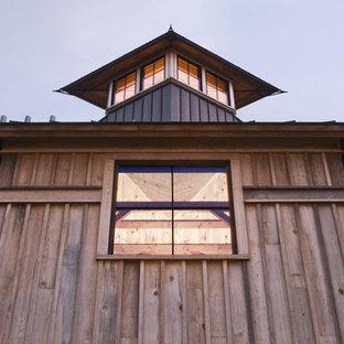 Imagen de fachada de casa roja, ecléctica, extra grande, de tres plantas, con revestimientos combinados, tejado a dos aguas y tejado de metal
