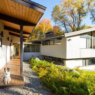 Foto de fachada gris, moderna, de tamaño medio, a niveles, con revestimiento de madera y tejado de un solo tendido