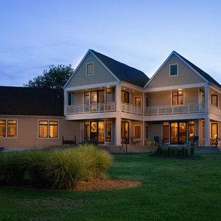 Imagen de fachada de casa verde, nórdica, con revestimiento de aglomerado de cemento, tejado a dos aguas y tejado de teja de madera