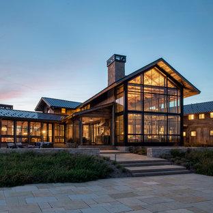 Неиссякаемый источник вдохновения для домашнего уюта: двухэтажный, деревянный, коричневый частный загородный дом в стиле рустика с двускатной крышей, металлической крышей и черной крышей