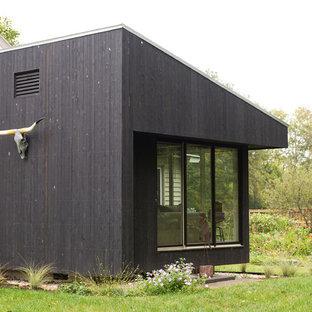 Foto della facciata di una casa piccola nera contemporanea a un piano con rivestimento in legno e tetto a una falda