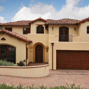 Inspiration for a large mediterranean yellow two-story stucco exterior home remodel in San Diego with a tile roof