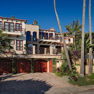 Mediterranean white three-story mixed siding house exterior idea in San Diego with a hip roof and a mixed material roof