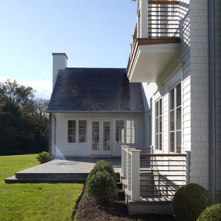 Large cottage white two-story vinyl gable roof idea in New York