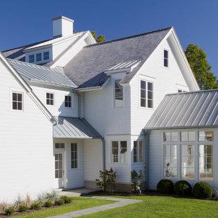 Foto della facciata di una casa grande bianca country a due piani con copertura mista, rivestimento in vinile e tetto a capanna