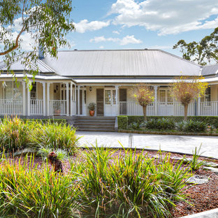 This is an example of a traditional one-storey white house exterior in Newcastle - Maitland with a hip roof and a metal roof.