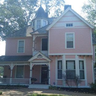 Exempel på ett mellanstort klassiskt rosa hus, med tre eller fler plan, vinylfasad och sadeltak