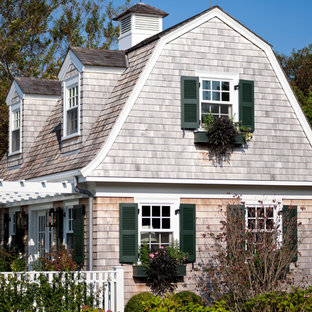 Ornate gray one-story wood exterior home photo in Other with a gambrel roof