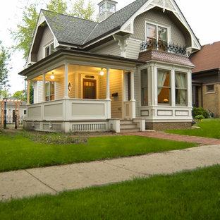 Свежая идея для дизайна: двухэтажный, серый частный загородный дом среднего размера в викторианском стиле с облицовкой из винила и крышей из гибкой черепицы - отличное фото интерьера