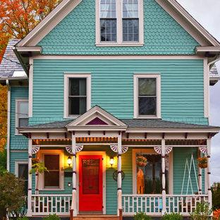 Foto della facciata di una casa unifamiliare blu vittoriana a tre o più piani con rivestimento in legno, tetto a capanna e copertura a scandole