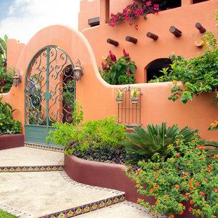 Inspiration pour une façade de maison orange méditerranéenne avec un revêtement en adobe.