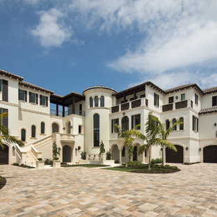 Huge tuscan white three-story stucco exterior home photo in Other with a tile roof and a hip roof