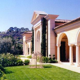 Ejemplo de fachada amarilla, mediterránea, grande, de dos plantas, con revestimiento de estuco y tejado a dos aguas