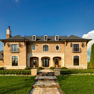 Example of a tuscan beige two-story brick exterior home design in Detroit with a hip roof